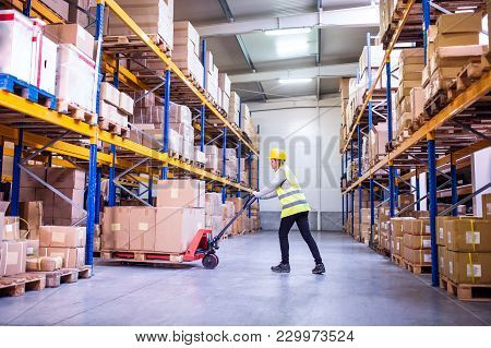 Young Woman Warehouse Worker With Hand Forklift Truck.