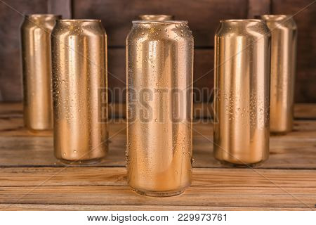 Cans of beer on wooden table