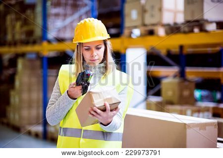 Warehouse Woman Worker Or Supervisor With Barcode Scanner. A Mobile Handheld Pc With Barcode Scanner