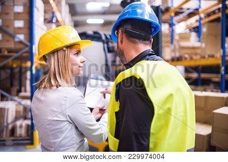 Young Workers Working Together In A Warehouse.