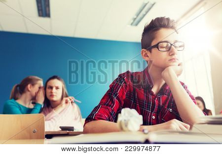 education, bullying, social relations and people concept - classmates gossiping behind student boy back at school