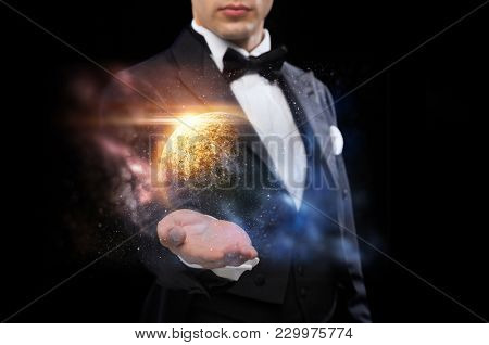 magic, imagination and people concept - male magician with planet and space hologram
