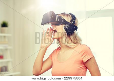 technology, virtual reality, entertainment and people concept - happy young woman in virtual reality headset or 3d glasses and headphones playing game at home and calling somebody out
