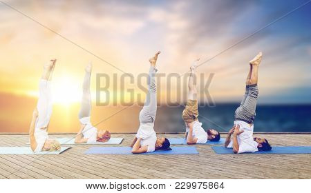fitness and healthy lifestyle concept - group of people doing yoga supported shoulderstand pose on mat outdoors on wooden pier over sea background