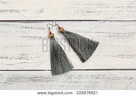 Gray Tassel Earrings On White Wooden Background