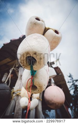 Close Up Image Group Of Dirty White Fish Net Buoy Tied With Rope, Hanging Under Wooden Cottage Over