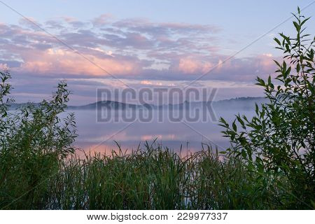 River With Fog And Pink Clouds And Frame Of Green Coastal Thickets At Dawn In Summer.
