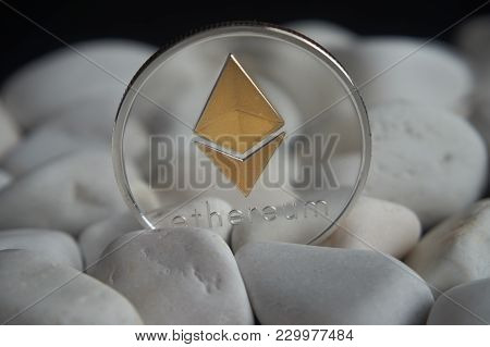 Silver Ethereum Coin Stuck Between White Stones. Cryptocurrency Mining Concept, Selective Focus.