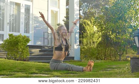 Professional Performance Of Asana Yoga By A Informal Look Young Girl In The Backyard Of Her House.