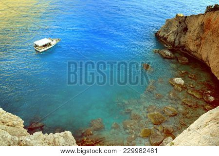 Greece summer coastline view. Blue sea water, rocky mountain and boat