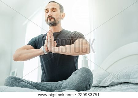 Find Yourself. Calm Healthy Occupied Man Sitting In The Bright Room On The Bed Holding Hands Opposit