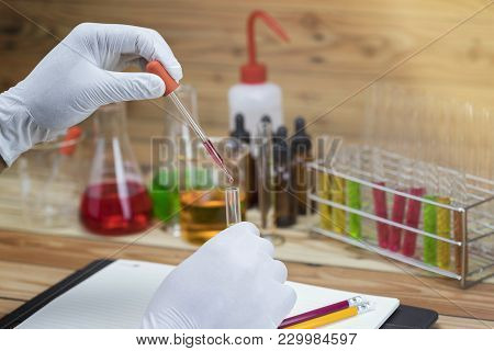 Researcher Is Dropping The Reagent Into Test Tube.scientist Working At The Laboratory.