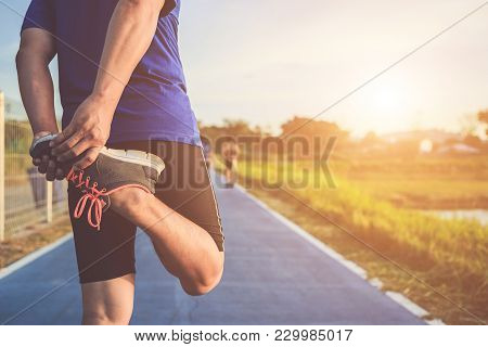 Man Workout And Wellness Concept : Asian Runner Warm Up His Body Before Start Running On Road In The