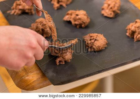 Someone Putting The Cookie Dough On The Pan To Bake