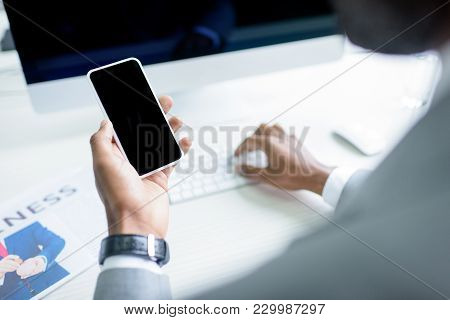 Partial View Of Businessman Using Smartphone At Workplace