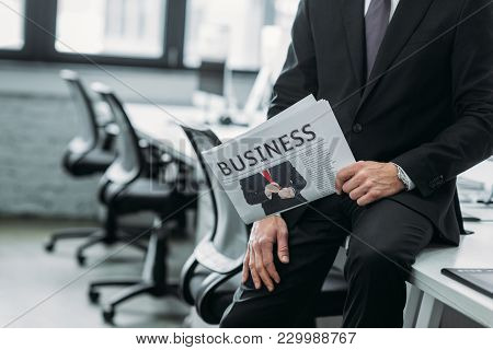 Partial View Of Businessman With Newspaper Sitting On Table In Office