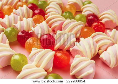 Closeup of heap of marshmallows and colourful sweets on pink background. Confectionery store advertisement and sweet life concept. poster