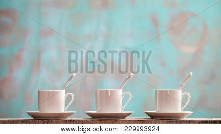 Three Small Porcelain Cups With Spoons And Saucers Against A Rustic Green Background With Copy Space