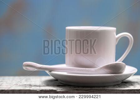 Porcelain Coffee Cup With Spoon And Saucer Against A Rustic Background With Copy Space