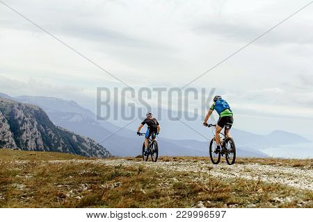 Two Cyclists Mountainbiker Riding Of Background Mountain Peaks