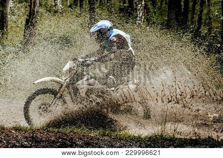 Enduro Motorcycle Racer Riding Puddle Splashes Mud And Water