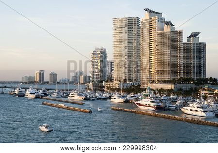 The View Of A Motorboat Passing By Miami Beach Marina At Dusk (florida).