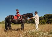 girl and father withe black stallion in a field poster