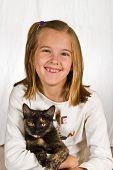 Pretty little girl holding her pet cat. poster