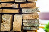 Stack of building lumber at construction site with narrow depth of field. Timber wooden bars. poster
