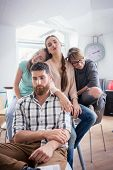 Funny group portrait of four sad or sleepy young people suffering of depression or workplace demotivation during work in a co-working office space poster