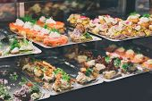 Danish smorrebrod traditional open sandwich at Copenhagen food market store. Many sandwiches on display with seafood and meat, smoked salmon. poster