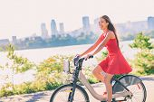 City bike young woman biking riding bicycle in street outdoors in summer with city skyline. Happy multiracial Asian girl active living a healthy lifestyle. Urban living, commute going to work. poster