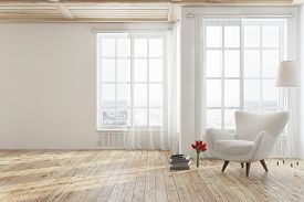 Empty White Living Room Interior With A Wooden Floor, Tall Windows And A White Armchair Near A Stack