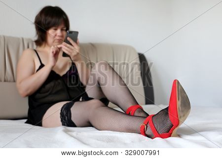 Woman In Black Lingerie And Red Shoes On High Heels Using Smartphone On A Bed. Concept Of Online Add