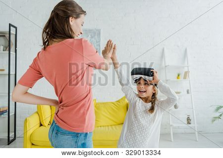 Cheerful Kid In Virtual Reality Headset Giving High Five To Babysitter At Home