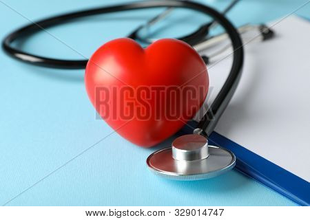 Stethoscope And Red Heart On Blue Background, Close Up. Healthcare