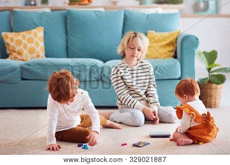 Cute Kids, Siblings Playing On The Floor At Home