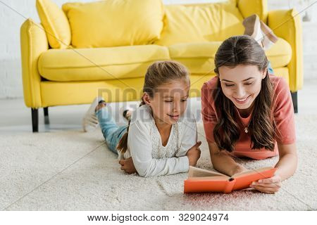 Happy Babysitter Lying On Carpet With Smiling Kid While Reading Book