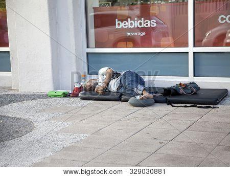 Bayamon, Puerto Rico/usa - February 10, 2019: Pan Handling Man Sleeps On A Mat On The Sidewalk.