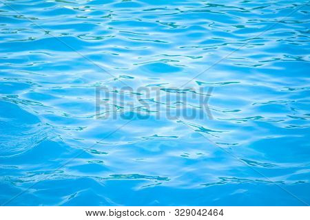 Surface Of Blue Swimming Pool Background Of Water In Swimming Pool. Simulate Natural Wave Ocean Wate