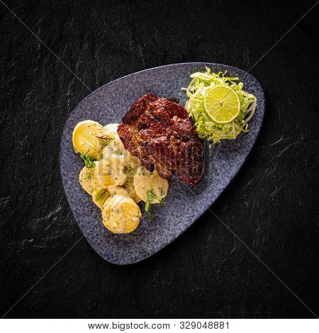 Grilled Mangalica Pork Chop Served With Creamy Potatoes In Butter And Iceberg Lettuce With Lime