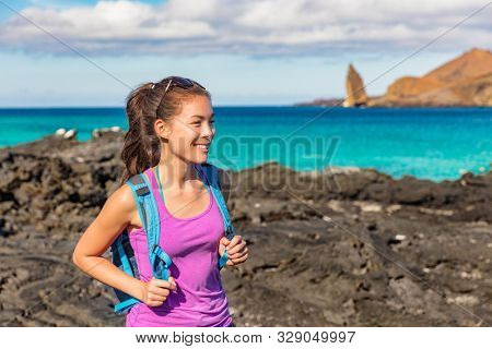 Galapagos tourist on Santiago Island in Galapagos Islands. Pinnacle Rock and Bartolome Island in background. Famous Galapagos cruise ship tour destination.