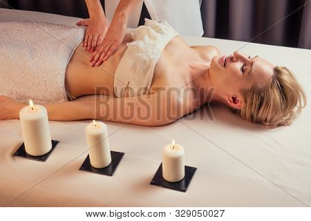 Anti Cellulite Belly Tantra Massage For Young Woman In Beauty Salon Next To The Candle Fire