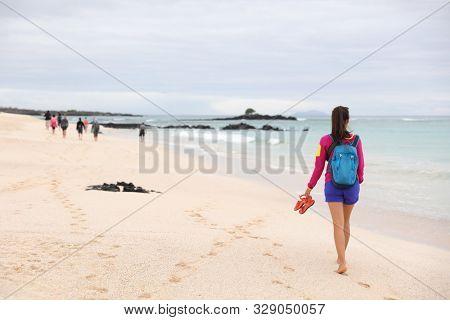 Galapagos Islands - woman on cruise ship tour visiting Playa las Bachas Beach on Santa Cruz Island. Woman walking barefoot in sand enjoying pristine nature landscape ecotourism poster