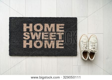 New home moving in door mat entrance welcome doormat with text writing HOME SWEET HOME and white sneakers of happy condo homeowner. Top view of rug and wooden floor.