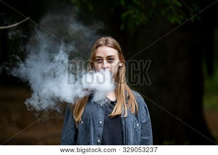 Vape Teenager. Young White Addict Caucasian Teenage Girl With Bruises Under The Eyes In Casual Cloth