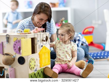 Cute Toddler Baby Girl Playing With Busyboard. Teacher Or Babysitter Teaching Kid In Nursery. Childr