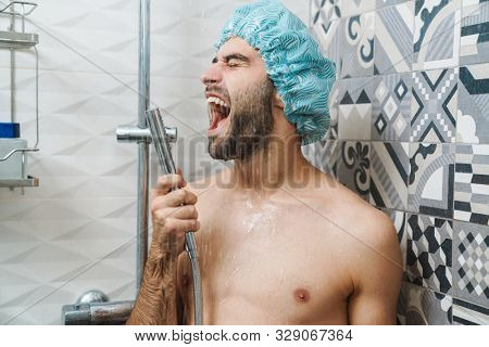 Attractive young cheerful man singing while washing in the shower, wearing shower cap and holding shower head