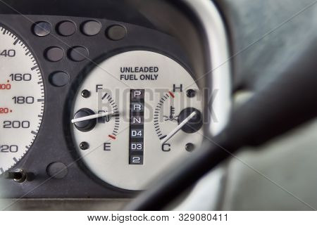 Car Dashboard With Text Unleaded Fuel Only. Fuel Level And Temperature Gauges Close-up