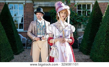 Handsome Man And Beautiful Woman Dressed In Vintage Clothing, Standing In Front Of Stately Brick Hom